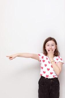 Schattige lachende jongen meisje in wit t-shirt met rode harten, stijlvolle zwarte spijkerbroek verwonderd haar vinger op zoek naar de zijkant