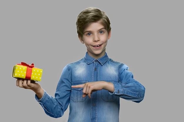 Schattige lachende jongen met geschenkdoos. knap jongetje wijzend op geschenkdoos met vinger terwijl hij tegen een grijze achtergrond. vakantie verrassing concept.