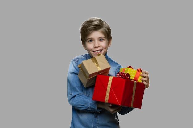 Schattige lachende jongen met geschenkdozen. portret van een kind met een stapel huidige dozen over grijze achtergrond. winter vakantie vieren.