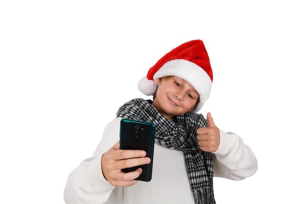 Schattige lachende jongen met rode kerstmuts selfie te nemen