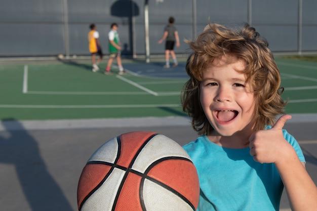 Schattige lachende jongen speelt basketbal toon duimen omhoog teken schattige lachende jongen speelt basketbal