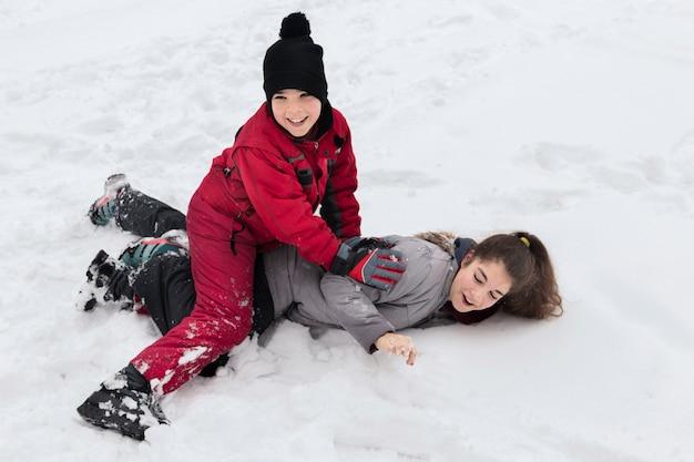 Schattige lachende jongen speelt met haar zus op besneeuwde grond op winterdag