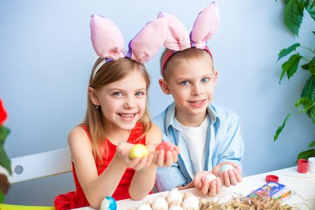 Schattige lachende kinderen, blonde broer en zus van 7-9 jaar oud, dragen konijnenoren op hun hoofd en schilderen paaseieren