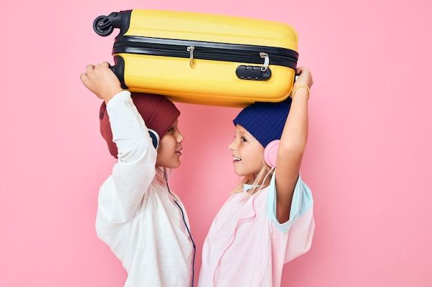 Schattige lachende kinderen met een gele koffer in zijn handen geïsoleerde achtergrond