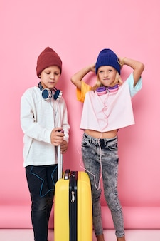 Schattige lachende kinderen stijlvolle kleding koffer hoofdtelefoon studio poseren