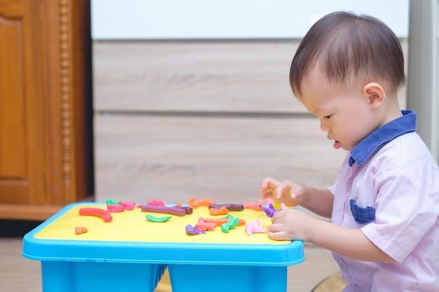 Schattige lachende kleine aziatische peuter jongen kind plezier spelen boetseerklei thuis