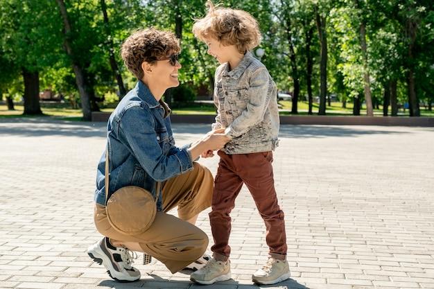 Schattige lachende kleine jongen en zijn gelukkige jonge moeder kijken elkaar terwijl plezier in openbaar park op zonnige zomerdag