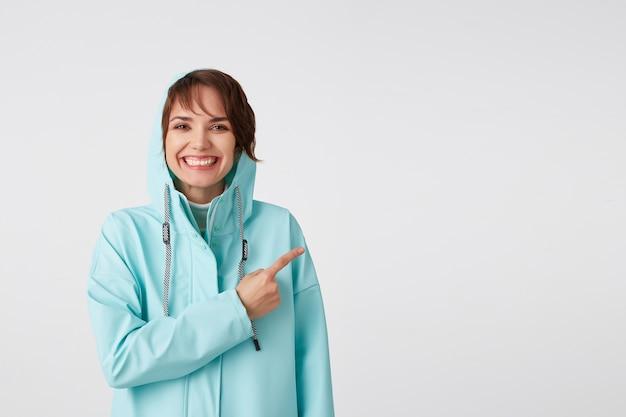 Schattige lachende kortharige krullende dame in blauwe regenjas, wil je aandacht vestigen op de kopie ruimte aan de rechterkant en naar hem wijzend, staat op een witte achtergrond.