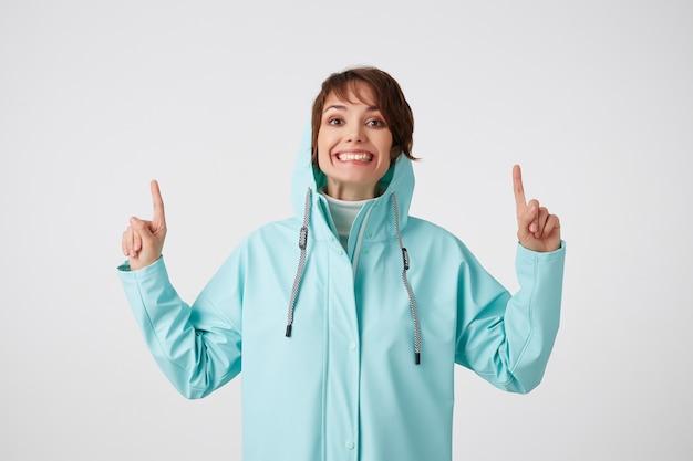 Schattige lachende kortharige krullende dame in blauwe regenjas, wil je aandacht vestigen op de kopie ruimte onder haar hoofd, staat op een witte achtergrond.