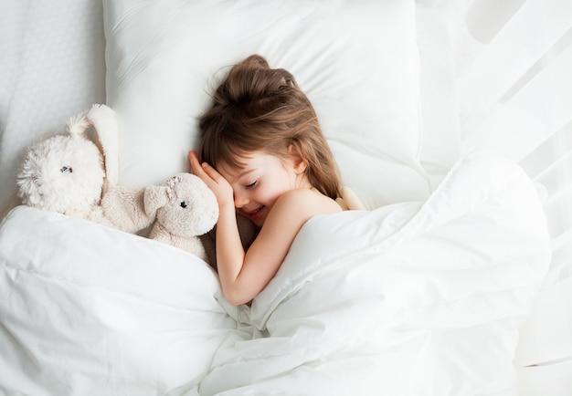 Schattige lachende meisje slapen in wit bed met konijn speelgoed in de buurt van haar