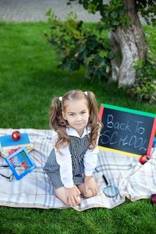 Schattige lachende schoolmeisje zittend op het gras met lunch, boeken in de buurt van de school. terug naar school. onderwijs concept. voorschoolse educatie. kopieer ruimte. klein meisje tijdens de lunch en leert op een gazon in het park.