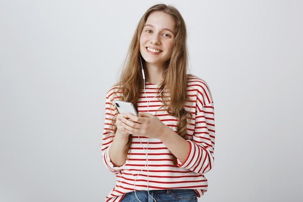 Schattige lachende tienermeisje met behulp van mobiele telefoon en muziek luisteren in oortelefoons