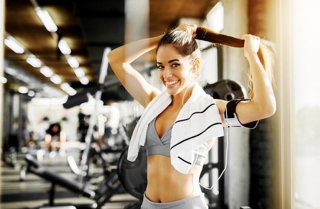 Schattige lachende vorm fitness meisje haar haren voorbereiden op oefening in de sportschool en kijken naar de camera.