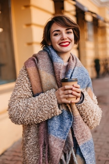 Schattige lachende vrouw koffie drinken in koude dag