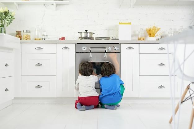 Schattige latijns-amerikaanse jongens, tweeling kijken naar taart bakken in de oven, hurken in de keuken thuis. kinderen, kookconcept. achteraanzicht