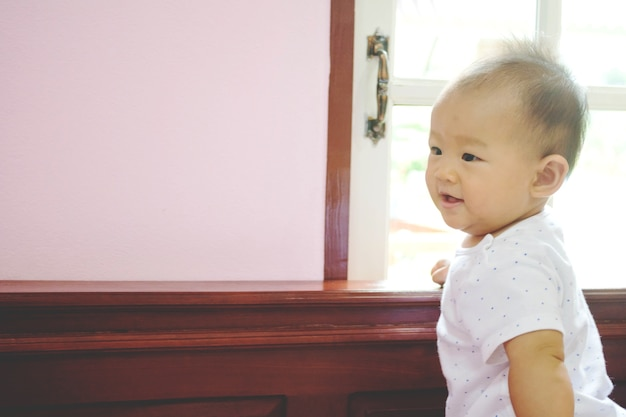 Schattige lieve aziatische baby draagkracht en glimlachend in de buurt van venster