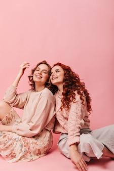 Schattige meisjes die op roze achtergrond met blij gezichtsuitdrukking zitten. studio shot van vrolijke vrienden.