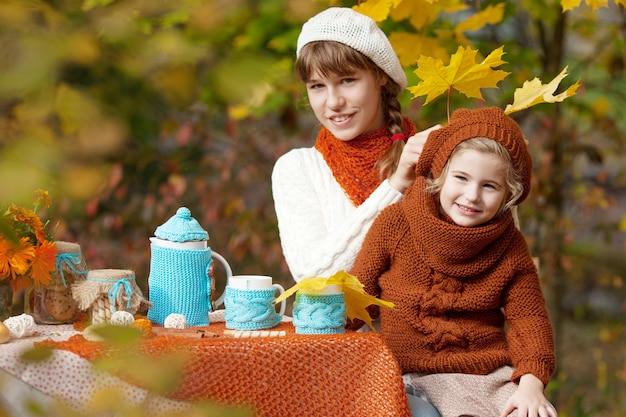 Schattige meisjes met theekransje buiten in de herfsttuin
