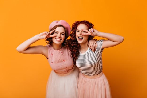 Schattige meisjes poseren met vredestekens. vooraanzicht van vrolijke stijlvolle dames gebaren op gele achtergrond.