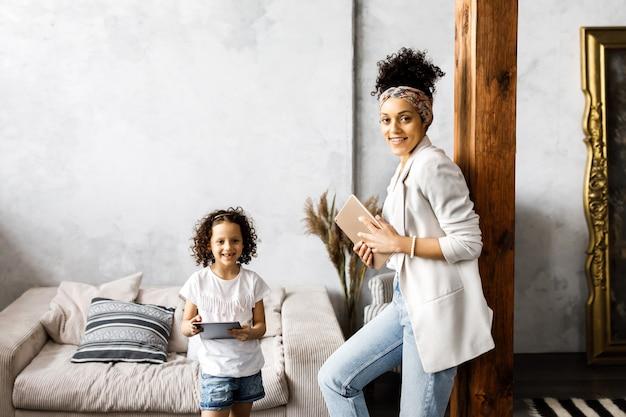 Schattige moeder en dochter praten en kijken naar de tablet terwijl ze in de woonkamer staan