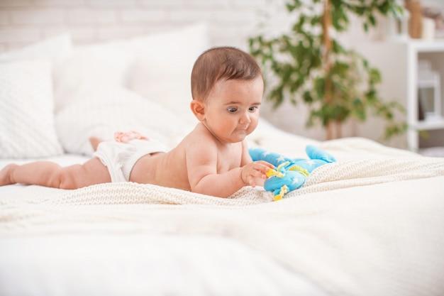 Schattige mollige baby ligt op zijn buik en kijkt naar het speelgoed.