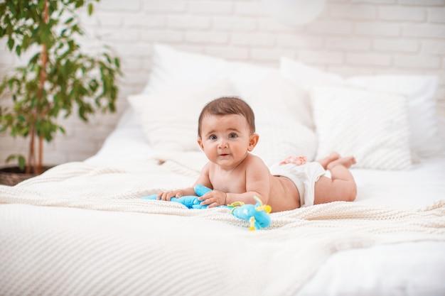 Schattige mollige baby ligt op zijn buik en kijkt weg