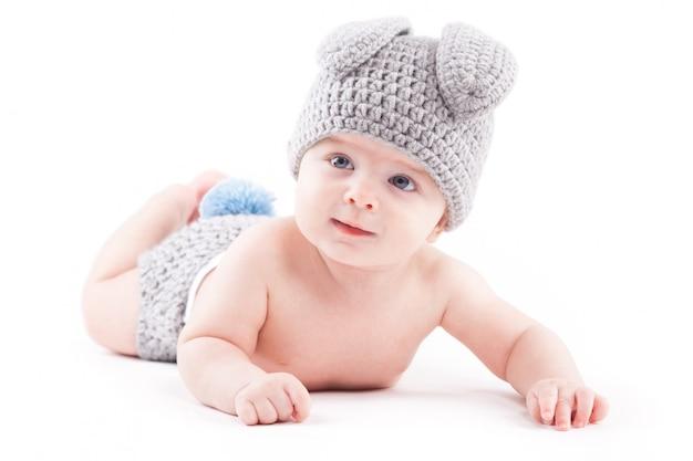 Schattige mooie babyjongen in haar kostuum ligt op buik