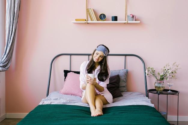 Schattige mooie brunette in een roze gewaad-shirt zit op het bed in de roze slaapkamer en houdt een kopje thee of koffie
