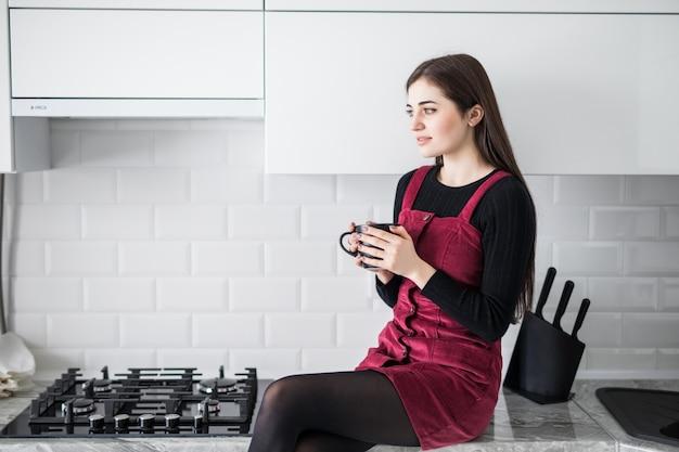 Schattige mooie charmante meisje, drinken koffie, zittend op tafel aanrecht in moderne licht witte keuken