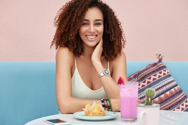 Schattige mooie jonge afro-amerikaanse vrouw met donker krullend kapsel, recreëert of besteedt vrije tijd in coffeeshop