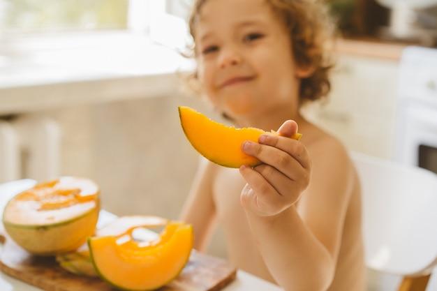Schattige mooie kleine jongen die verse meloen eet.