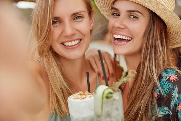 Schattige mooie lesbische vrouwen hebben positieve uitdrukkingen, maken een selfie met een onherkenbaar elektronisch apparaat, staan dicht bij elkaar, tonen goede relaties en liefde. rust concept