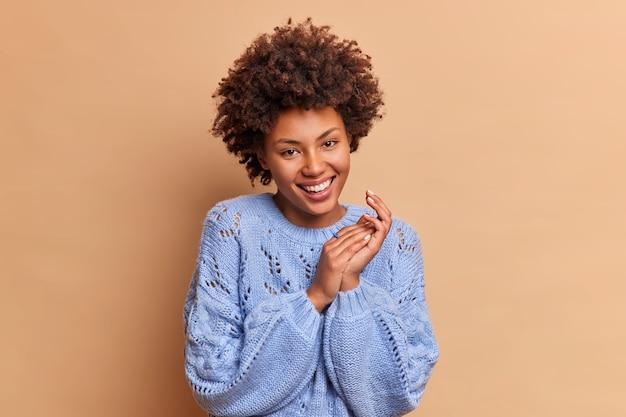 Schattige mooie vrouw met oprechte glimlach natuurlijk krullend afro haar handen wrijft en kijkt vrolijk naar voren exresses vreugde draagt casual trui geïsoleerd over beige muur
