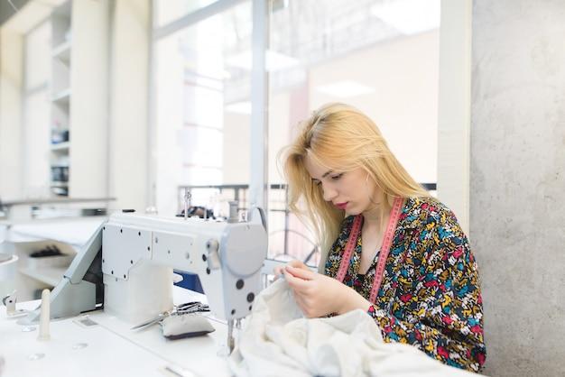 Schattige naaister werkt op de werkplek in de buurt van een naaimachine.