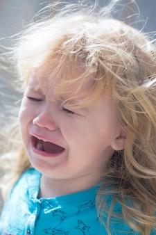 Schattige ongelukkige babyjongen met lang blond haar in blauwe tshirt huilen buiten op zonnige zomerdag