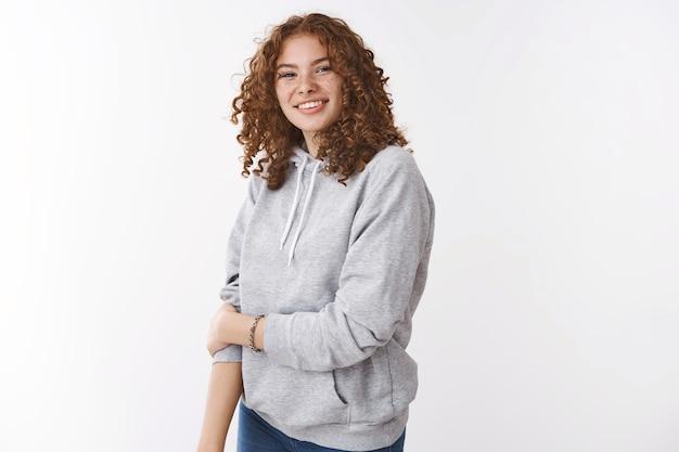 Schattige onzekere jonge roodharige tienermeisje met sproeten krullend haar dragen grijze hoodie glimlachend touch arm onzeker blozen grijnzend vriendelijk praten met nieuwe collega's, staande witte achtergrond