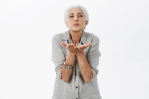 Schattige oude dame met grijze haar blazende luchtkus