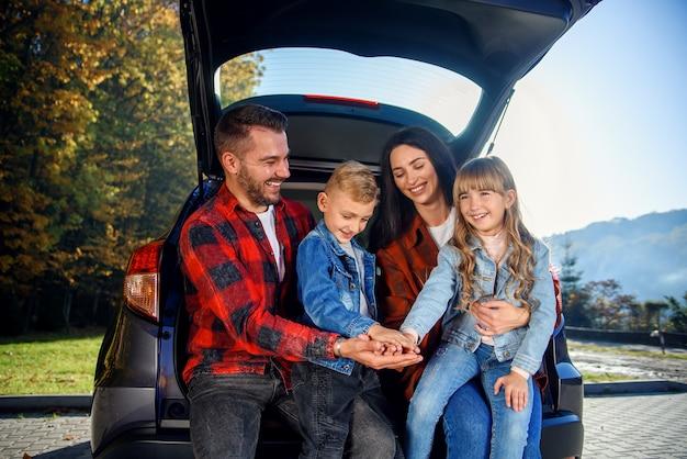 Schattige ouders met hun lieve kinderen die in de kofferbak van hun gezinsauto zitten te lachen en elkaar vijf te geven.