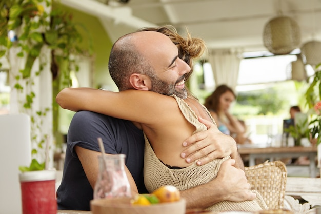 Schattige paar genieten van samenzijn, elkaar teder knuffelen. stijlvolle vrouw omhelst haar bebaarde vriendje en feliciteert hem met promotie op het werk.