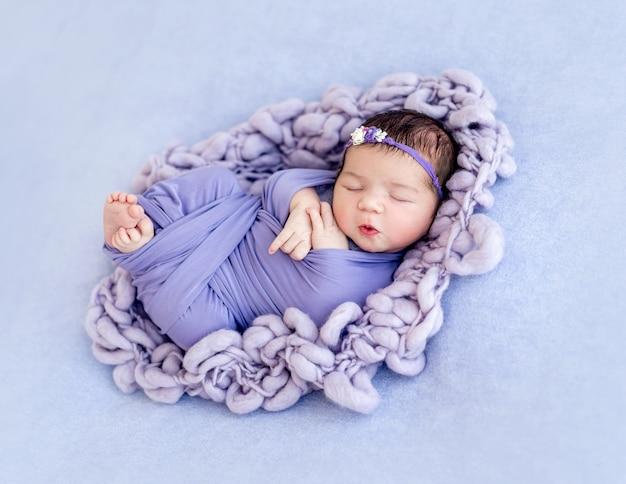 Schattige pasgeboren baby in paars gewikkeld