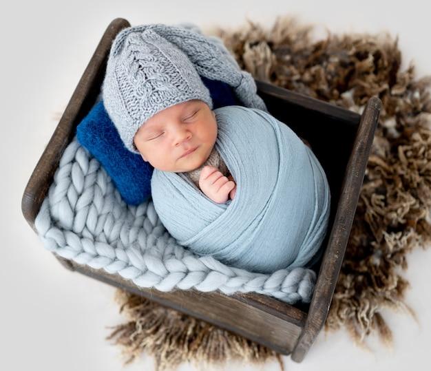 Schattige pasgeboren babyjongen ingebakerd in stof en het dragen van schattige gebreide muts slapen in houten gestileerde bed in studio. baby kind dat binnen slaapt