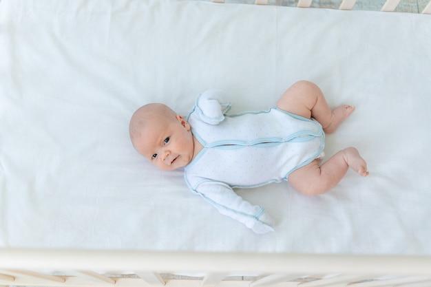 Schattige pasgeboren babyjongen liggend op de achterkant van de wieg op het katoenen bed thuis voordat hij naar bed gaat, babyweek, het concept van geboorte en kinderschoenen, bovenaanzicht.