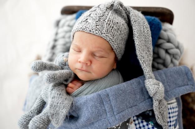 Schattige pasgeboren babyjongen met een schattige gebreide muts die slaapt en konijntjesspeelgoed in kleine handen houdt tijdens de studiofotoshoot. baby kind dat binnen slaapt