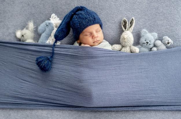 Schattige pasgeboren babyjongen met schattige gebreide muts slapen onder stof met schattig handgemaakt speelgoed. baby kind dat binnen slaapt