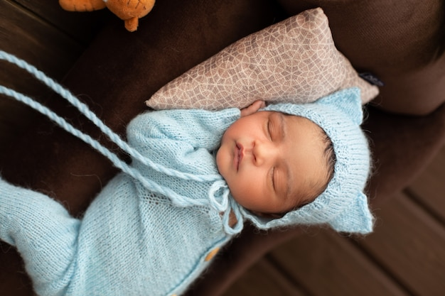 Schattige pasgeboren mooie en sympathieke babyjongen die op bruine bank en hoofdkussen in blauwe gehaakte pijamas slaapt