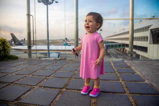 Schattige peuter baby in een roze jurk huilt angstig verloren op de luchthaven. vliegtuigen op de achtergrond in onscherpte.