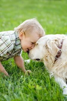 Schattige peuter blonde jongen met golden retriever buiten