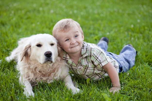 Schattige peuter blonde jongen met golden retriever knuffelen