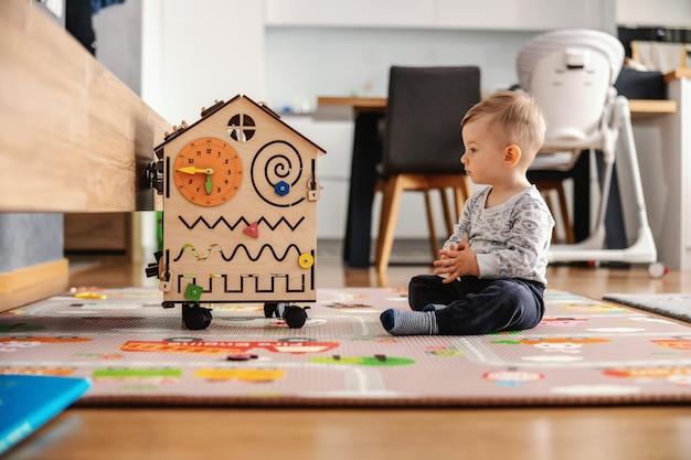 Schattige peuter die interactieve spelletjes speelt voor een goede ontwikkeling thuis.