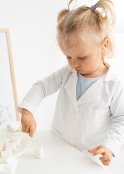 Schattige peuter die over wetenschap leert met marshmallows en pasta